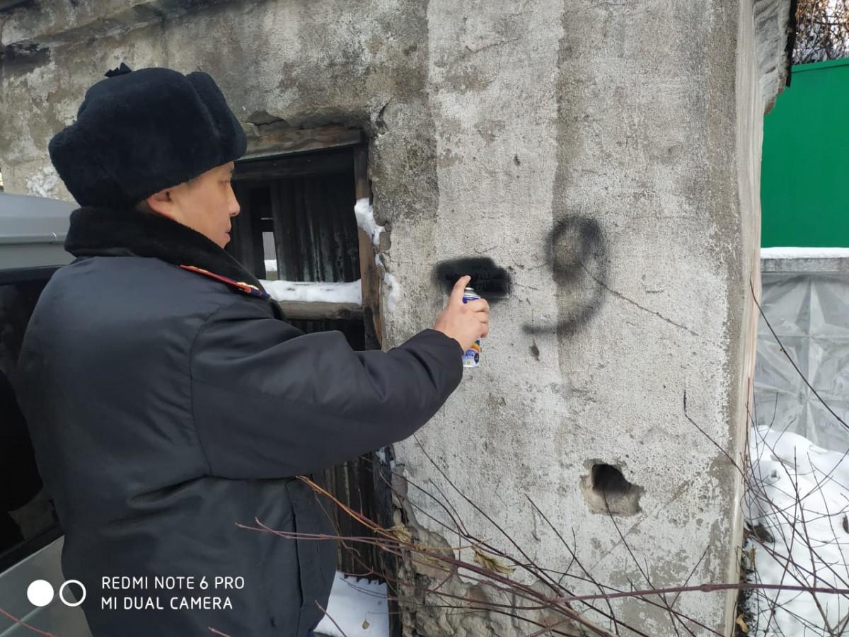 Участковые инспекторы Алматы закрашивают рекламу наркотиков